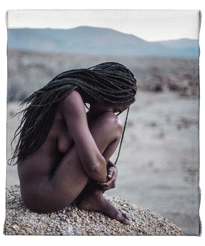 A nude Namibian model posing on a granite boulder in the Erongo Mountains in central Namibia